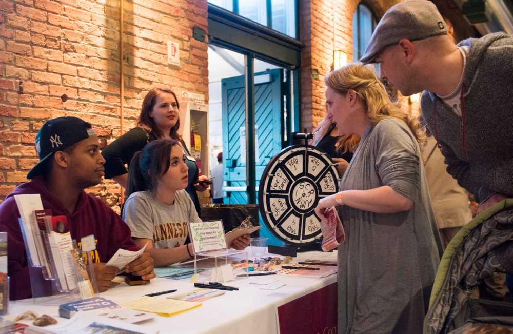 Student Neighborhood Liaisons senior Eskender Abebe and junior Megan Felz talk to third ward residents Sarah and Brandon Soderlund about the Student Community Relations group at the Third Ward Neighborhood Festival held at Nicollet Island Pavillion on Wednesday evening.