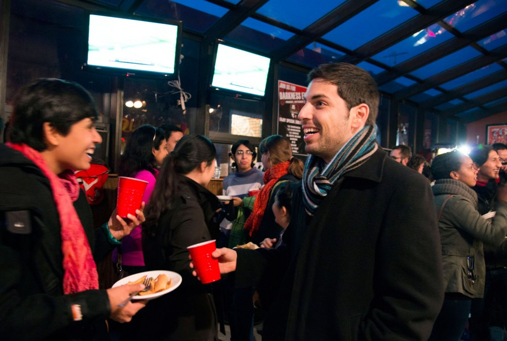 Graduate students Sarita Pillay and Naor Bitton share a laugh at a happy hour gathering organized by the Council of International Graduate Students (CIGS) on Monday at Stub and Herb's.