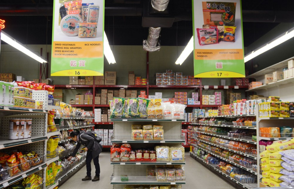 A shopper compares food items at United Noodles, a local Asian grocery store on Monday in Minneapolis.