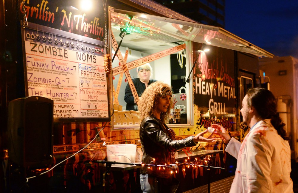 Lindsey Siebenaler serves samples in front of the Motley Crews Heavy Metal Grill Food That Rocks food truck at the Zombie Pub Crawl in Minneapolis on Saturday.