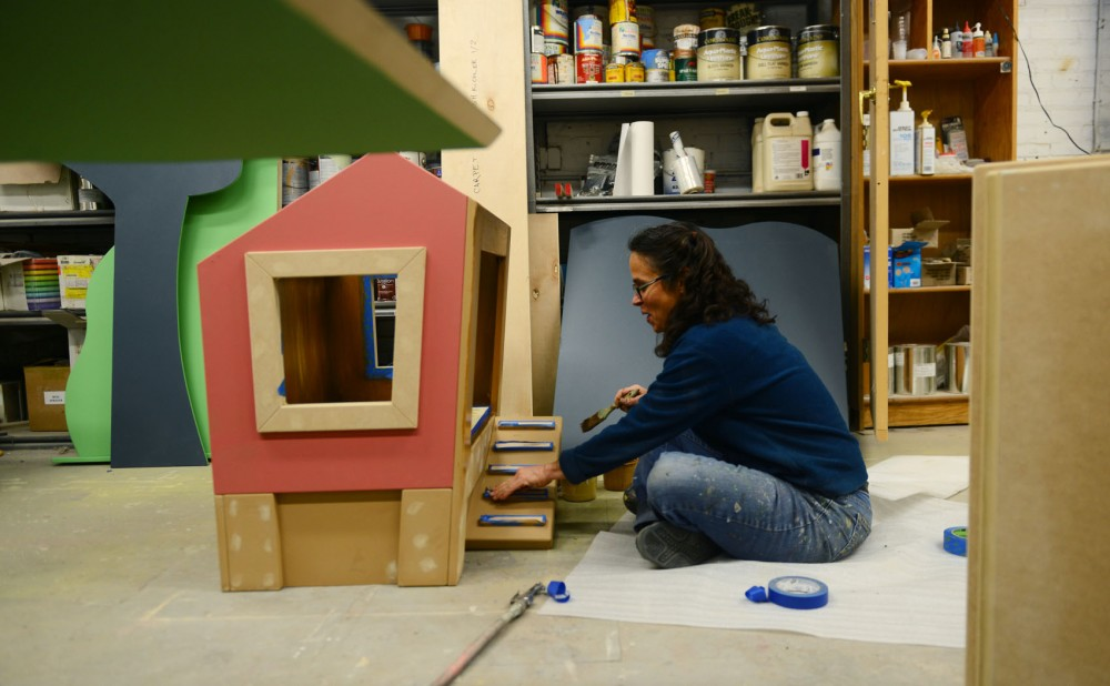 Scenic painter Julie Prairie paints a chicken coop for a farm area exhibit at KidZibits in Minneapolis on Wednesday. KidZibits builds exhibits for museums worldwide.