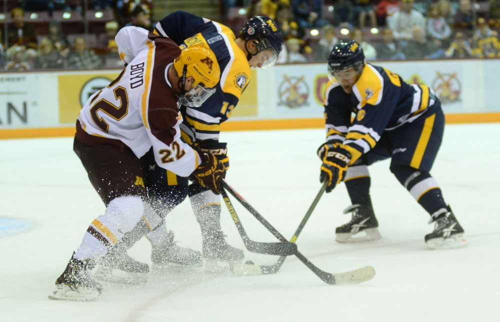 Minnesota froward Travis Boyd fights for the puck against Lethbridge on Saturday at Mariucci Arena.