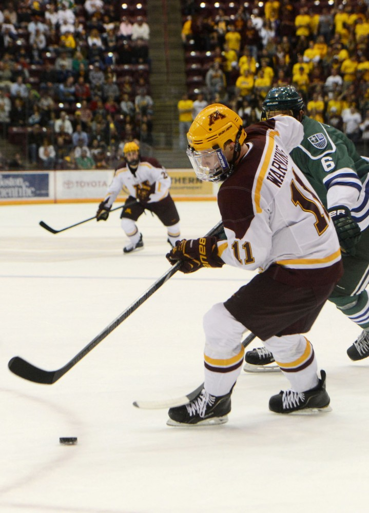 Minnesota forward Sam Warning handles the puck against Mercyhurst in the Ice Breaker Tournament at Mariucci Arena on Friday, Oct. 11, 2013.