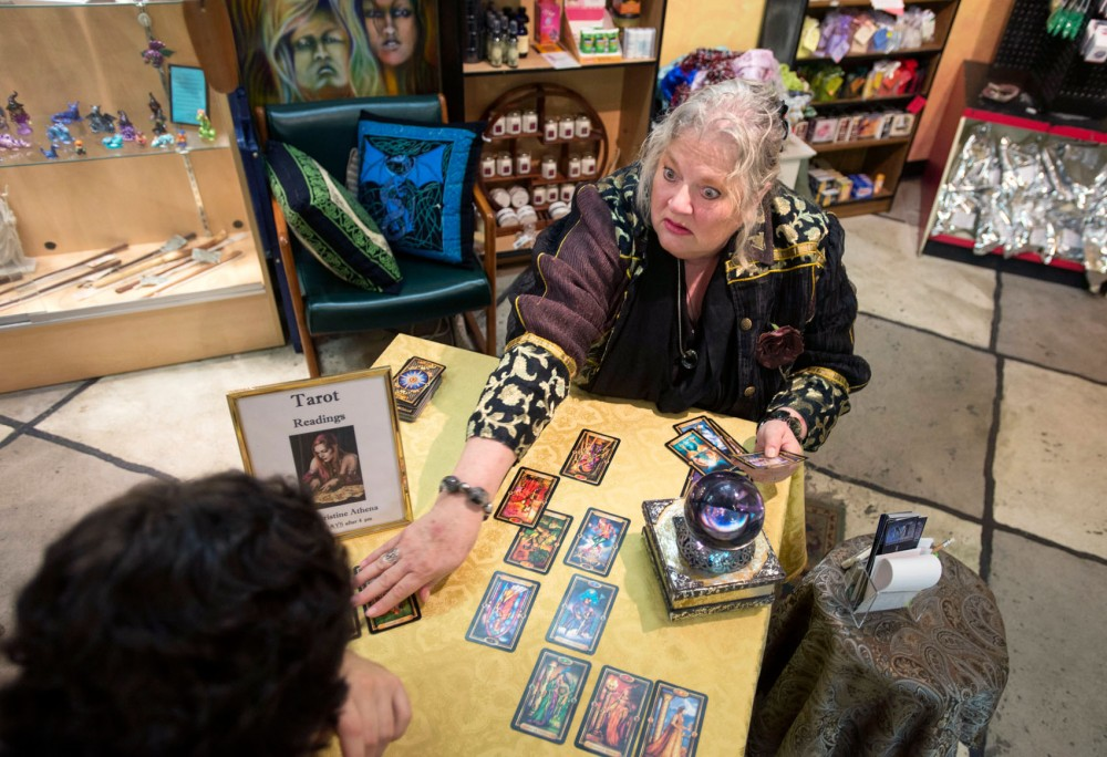 Psychic Christine Athena reads a client's tarot cards on Wednesday evening at Magus Books & Herbs.