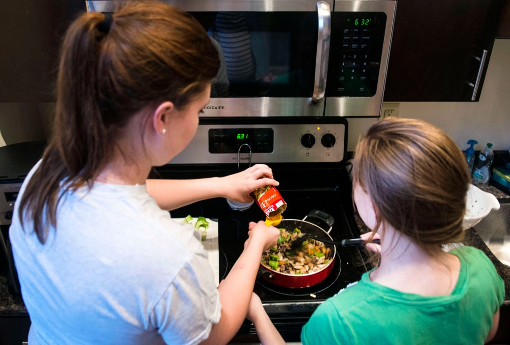 Junior economics major Mackenzie Hanson and junior architecture major Cozy Hannula add seasoning as instructed by SNAC members for a southwestern hash recipe on Thursday at their apartment.