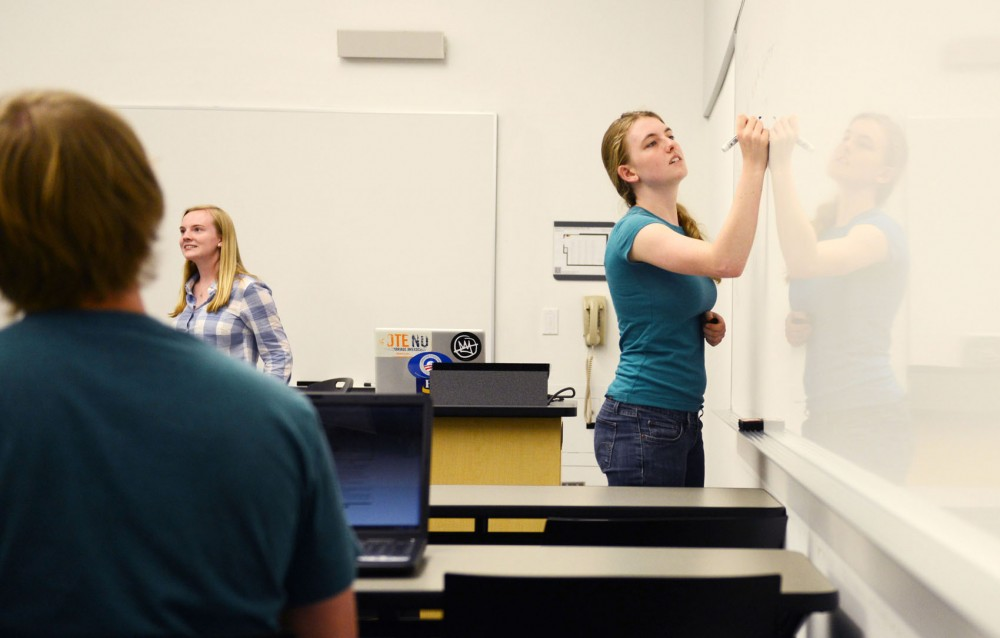 President of College Democrats Laura Pratt writes on a whiteboard while group members brainstorm ideas for an event that would educate students on ranked choice voting on Wednesday evening in STSS. The student group endorsed Mark Andrew and Jacob Frey.