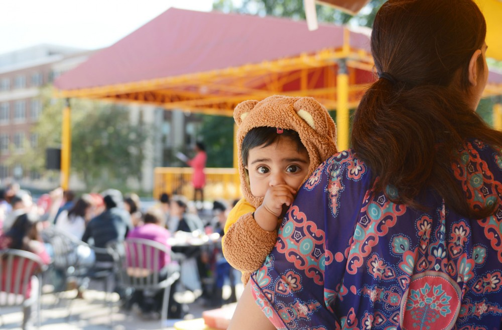 Baby gopher Zoyah Khan and her mother, senior psychology student Shazia Khan, listen to poetry by Ekere Tallie at Student Parent Visibility Day at Northrop Plaza on Wednesday. This event was hosted by the Student Parent Help Center in an effort to raise awareness about undergraduate students who are also parents.