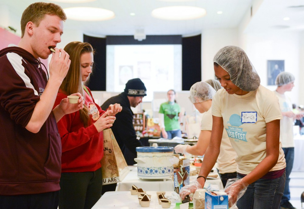 Freshmen pre-architecture majors Nathan Manske and Lanie Hei taste free samples of non-dairy soy ice cream sandwiches on Saturday at Coffman Union.