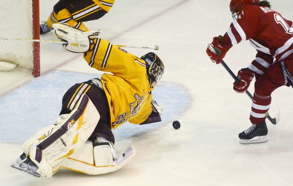 Minnesota sophomore goalie Amanda Leveille lunges to protect the goal against Wisconsin on Saturday, Oct. 12, 2013, at Ridder Arena.