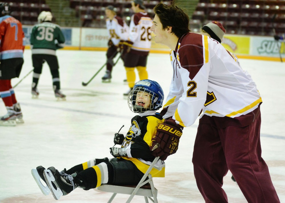 Minnesota defenseman Brady Skjei pushes Elliott Harding, a member of the Minnesota Special Hockey team Stingers, around the rink on Saturday at Mariucci Arena. The Hendrinkson Foundation worked with the University to join the men's hockey team with local sled hockey and special hockey teams.