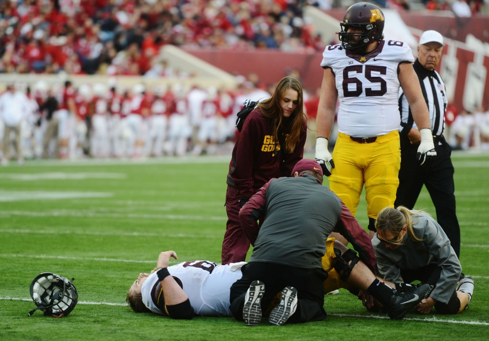 Minnesota medical staff tend to Gophers center Jon Christenson after a leg injury against Indiana at Memorial Stadium in Bloomington, Ind., on Saturday. Christenson is out for the season.