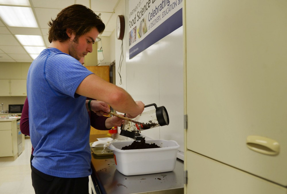 Junior Neil Horan pours coffee into a bucket of compost in his food science class in McNeal Hall on Thursday, Nov. 1, 2013.