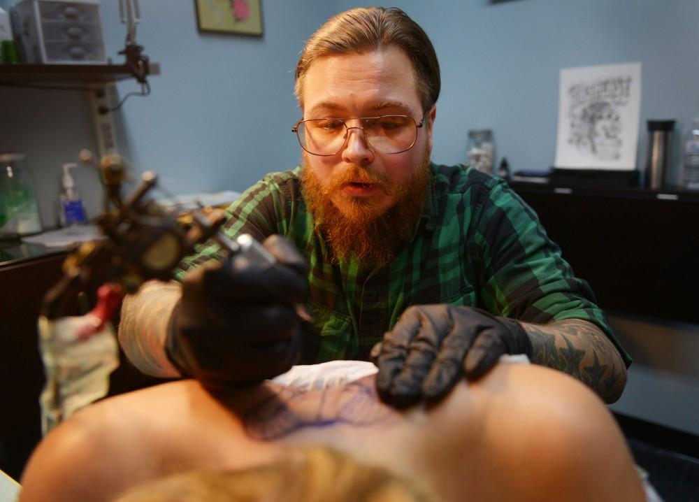 Northeast tattoo artist Spencer Hodgeson tattoos a rams skull onto Minnesota Daily reporter Emily Eveland's back on Monday, Nov. 11, 2013.