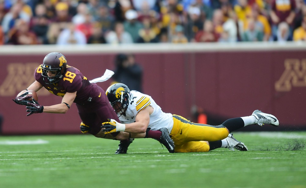 Minnesota wide receiver Derrick Engel is tackled by an Iowa player Saturday, Sept. 28, 2013, at TCF Bank Stadium.