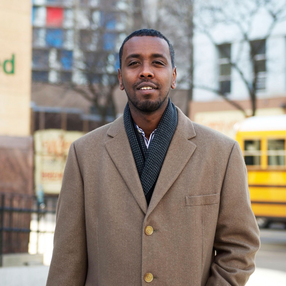 Abdi Warsame poses for a portrait on Riverside Avenue in front of the Riverside Plaza. Warsame is now the first Somali-American member of the Minneapolis City Council, representing the Cedar-Riverside region.