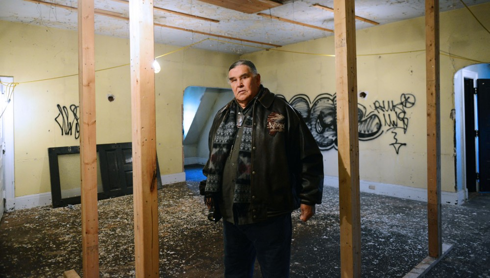 American Indian Movement National Director and co-founder Clyde Bellecourt poses in the 6,444 square foot Henry B Frey Mansion on Tuesday.  The organization is selling the mansion to raise funds to build a cultural center.