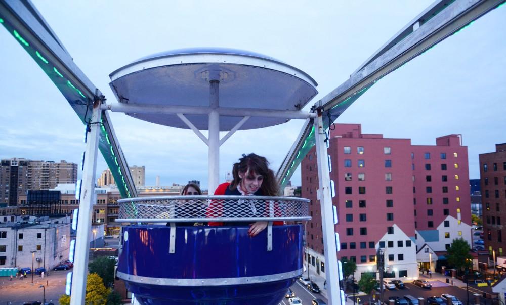 Lauren Gantner looks over the edge of a Ferris wheel in Minneapolis at the Zombie Pub Crawl on Saturday, Oct. 12, 2013.