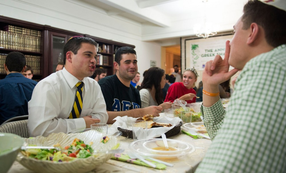 President of Alpha Epsilon Pi and senior Senior Seth Franklin and Alpha Epsilon Pi members Louis Livon-Bemel and Zack Gilbert Burke talk at the second annual Greek Shabbat dinner hosted at Chabad on Friday. Chabad welcomed students to celebrate Shabbat, a weekly Jewish holiday.