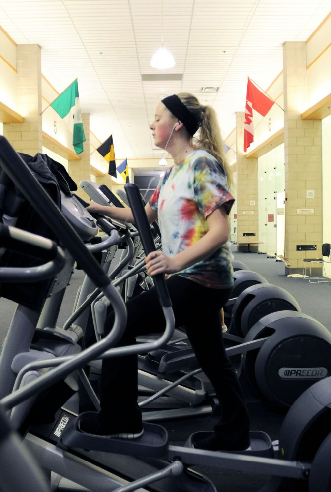 Journalism then-freshman Olivia Kurtz works out on an elliptical machine at the University Recreation Center on Thursday, April 4, 2013.