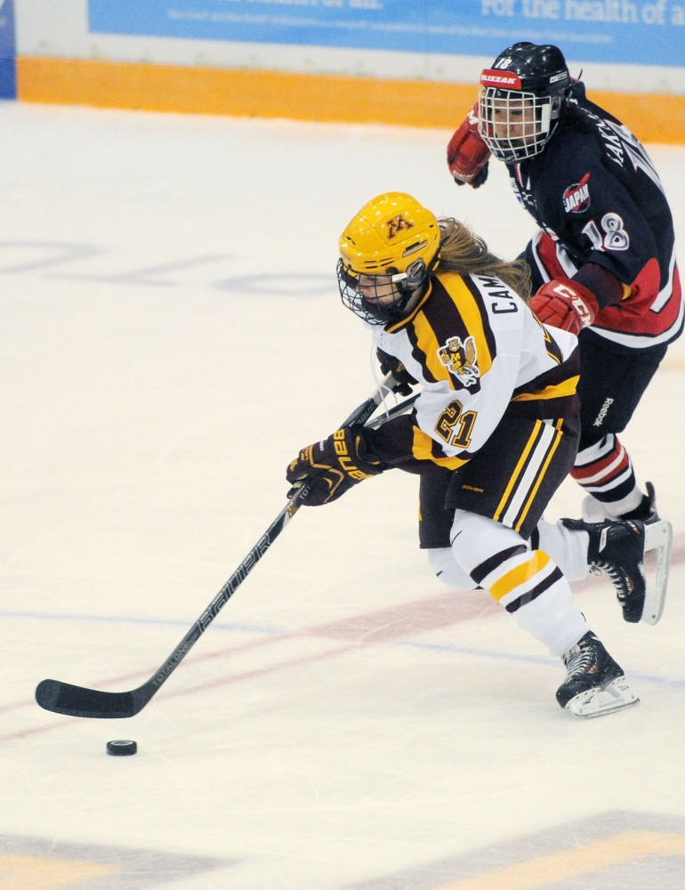 Gophers freshman forward Dani Cameranesi protects the puck from Team Japan at Minnesotas exhibition game Thursday, Sept. 26, 2013, at Ridder Arena.