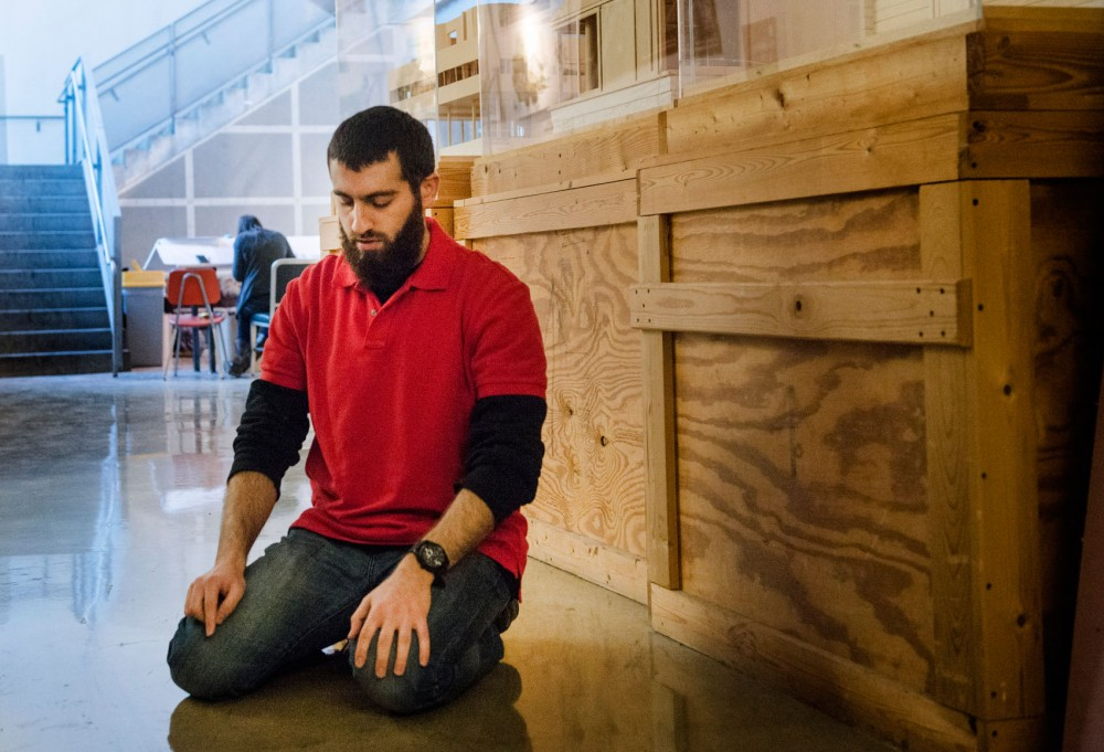 Muslim Student Association President and architecture senior Amer Sassila prays in a secluded area in Rapson Hall on Tuesday.