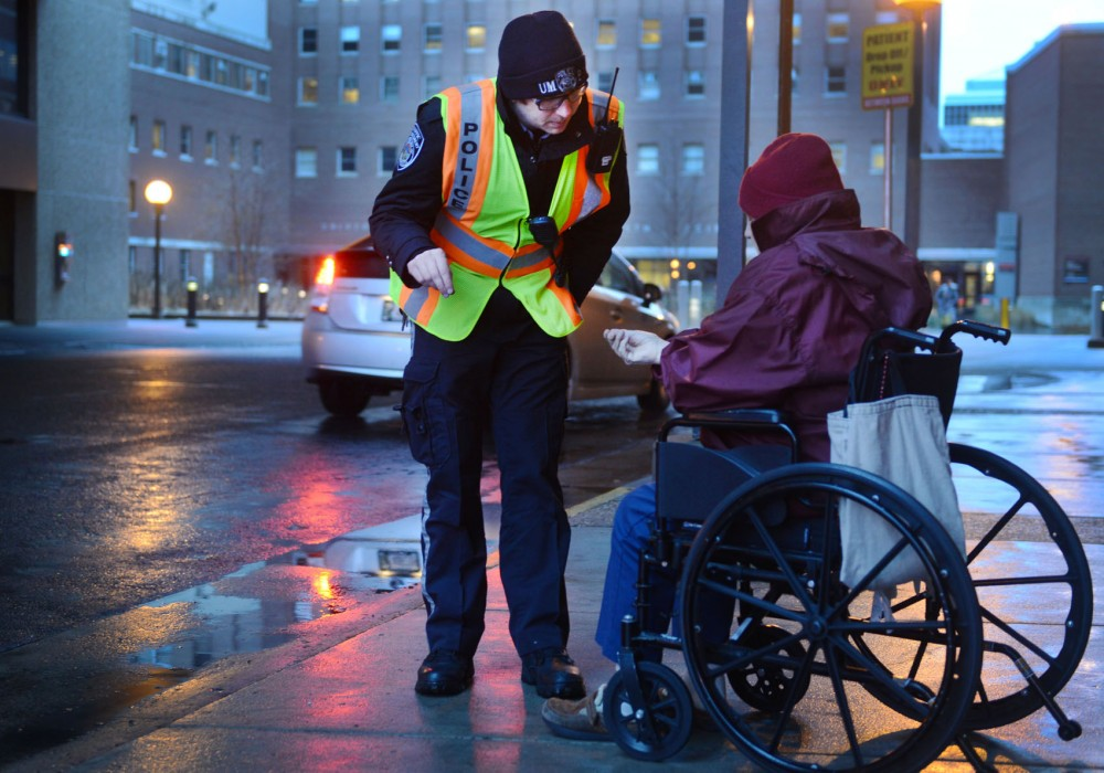University of Minnesota police officer Ryan Ross assists a pedestrian while directing traffic at Moos Tower on Tuesday.