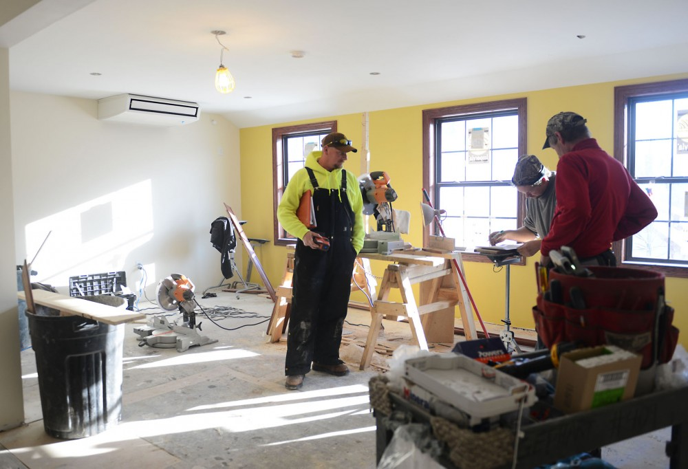 Construction workers work on the study area at the new Alpha Gamma Rho fraternity house in St. Paul on Monday. The chapter house has been closed this semester for a major renovation and members are anticipating the completion of it by January.