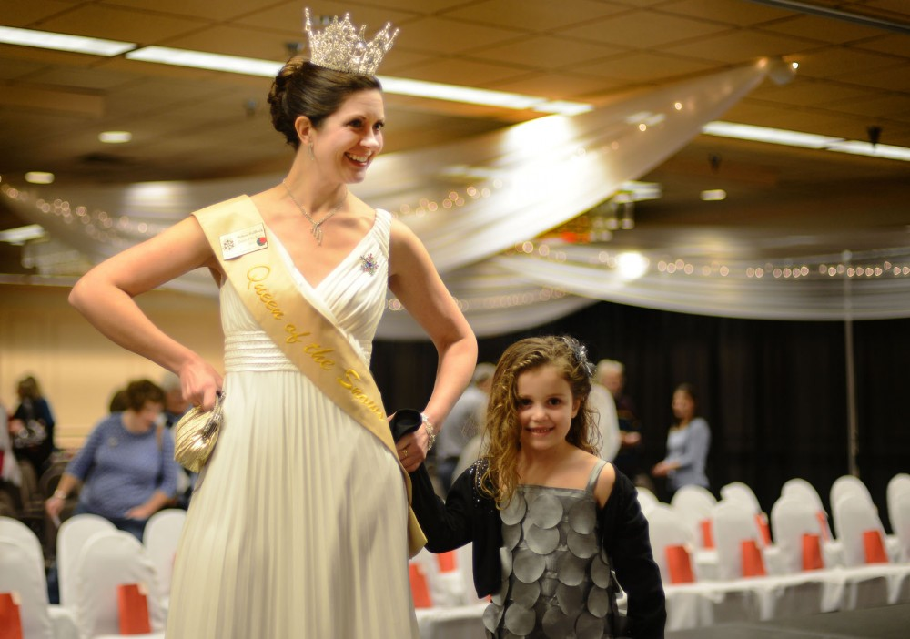 Queen of the Snows Melissa Hoffbeck shows a girl how to walk down the runway before the Queen of the Snows Crowns and Gowns Fashion Show at Jimmy's Event Center on Friday, Jan. 17, 2014. The St. Paul Winter Carnival begins this week, and the new Royal Family will be crowned Friday.