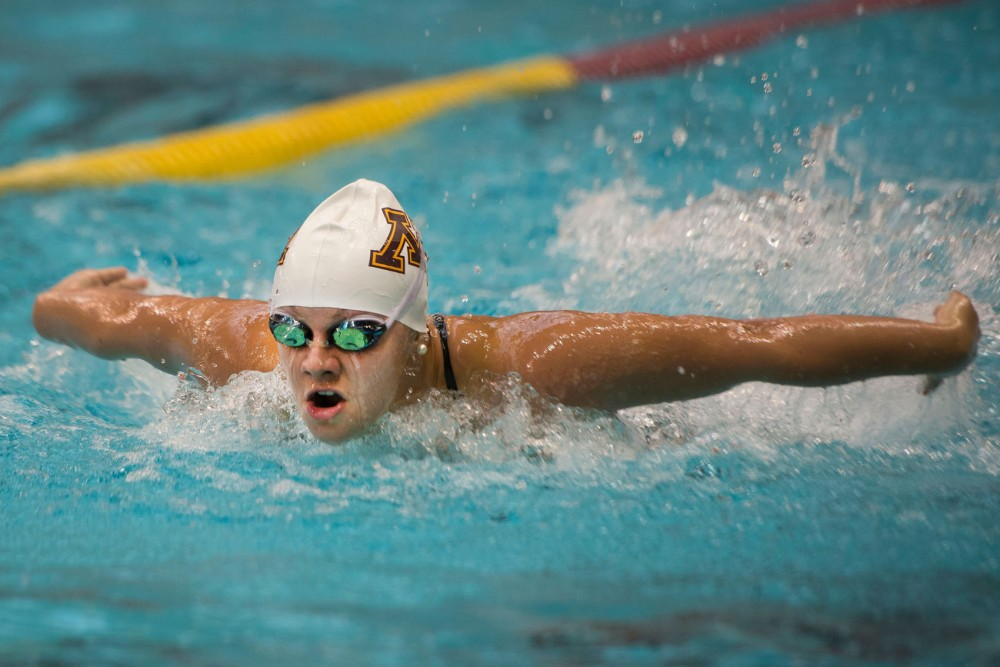 Freshman Allison Schumacher propels herself out of the water during the womens 100 yard butterfly event Saturday at the University Aquatic Center.