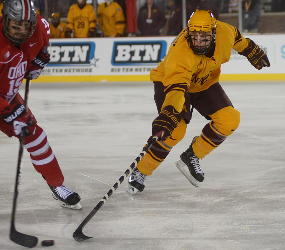 Minnesota defenseman Mike Reilly reaches for the puck against the Buckeyes on Friday at the Hockey City Classic at TCF Bank Stadium.
