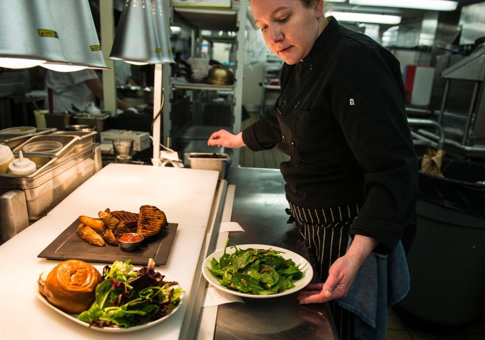 Chef Jen Farni prepares lunch entrees at the Minneapolis Institute of Arts Grain Stack restaurant Saturday.