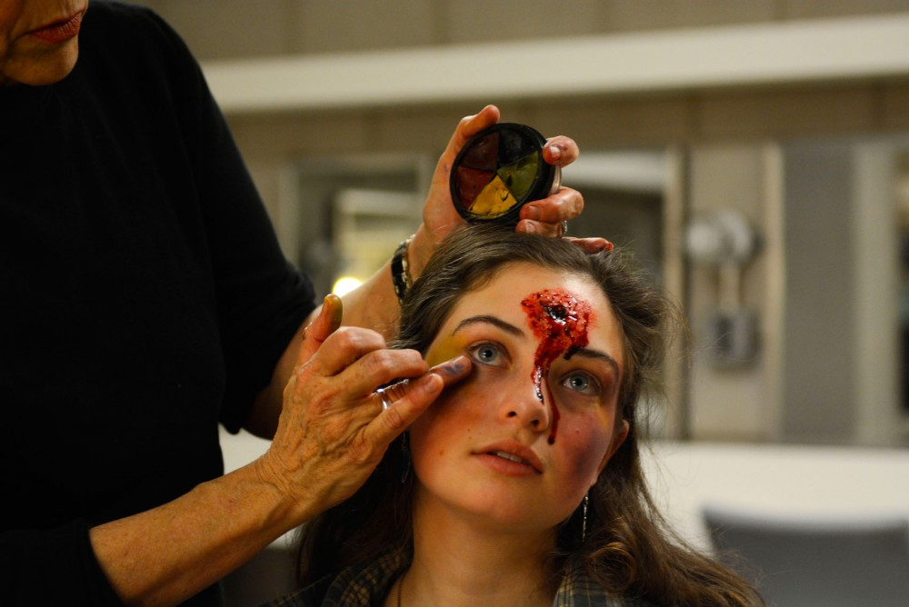 University professor and make-up artist Tessie Bundick demonstrates how to apply make-up to imitate a bruise on junior acting BFA student Rebecca Leiner in the Rarig Center on Friday.