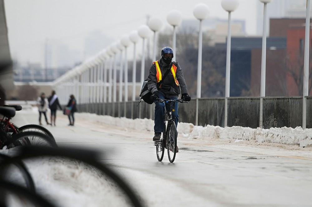 A biker travels across the Washington Avenue Bridge in subzero temperatures Sunday afternoon.