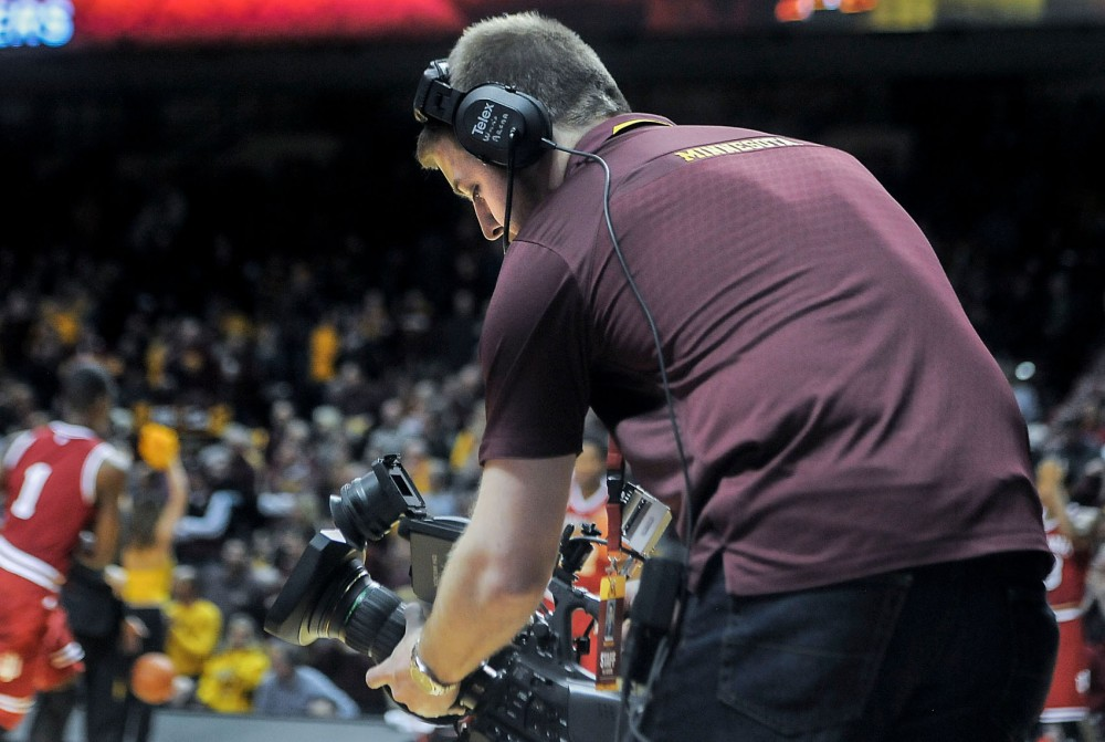 Gopher sports digital media producer Garrett Wright shoots video at the Minnesota men's basketball game against Indiana at Williams Arena Saturday.