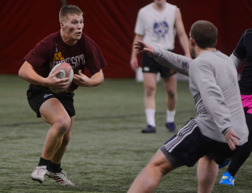 Gophers rugby player Alex Ringhand runs the ball at rugby practice at the Student Recreational Sports Dome on Tuesday evening. Rugby is a sport that does not use helmets, but concussions consistently interfere with sports throughout the country and have serious health implications.