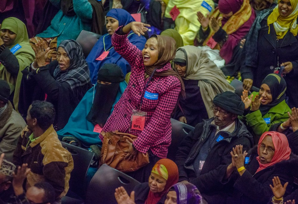 Participants cheer for Mohamud Noor as he discusses his platform at the reconvened precinct caucus event at Coffman Memorial Union on Wednesday.