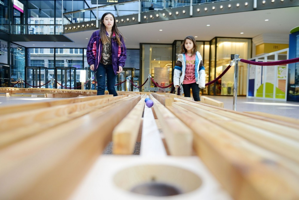 Val Birkeland, 13, and Kayla Birekland, 8, watch their balls roll near the hole at the U.S. Bank Skyway Open Sunday, a putt-putt golf course located in downtown Minneapolis skyways.