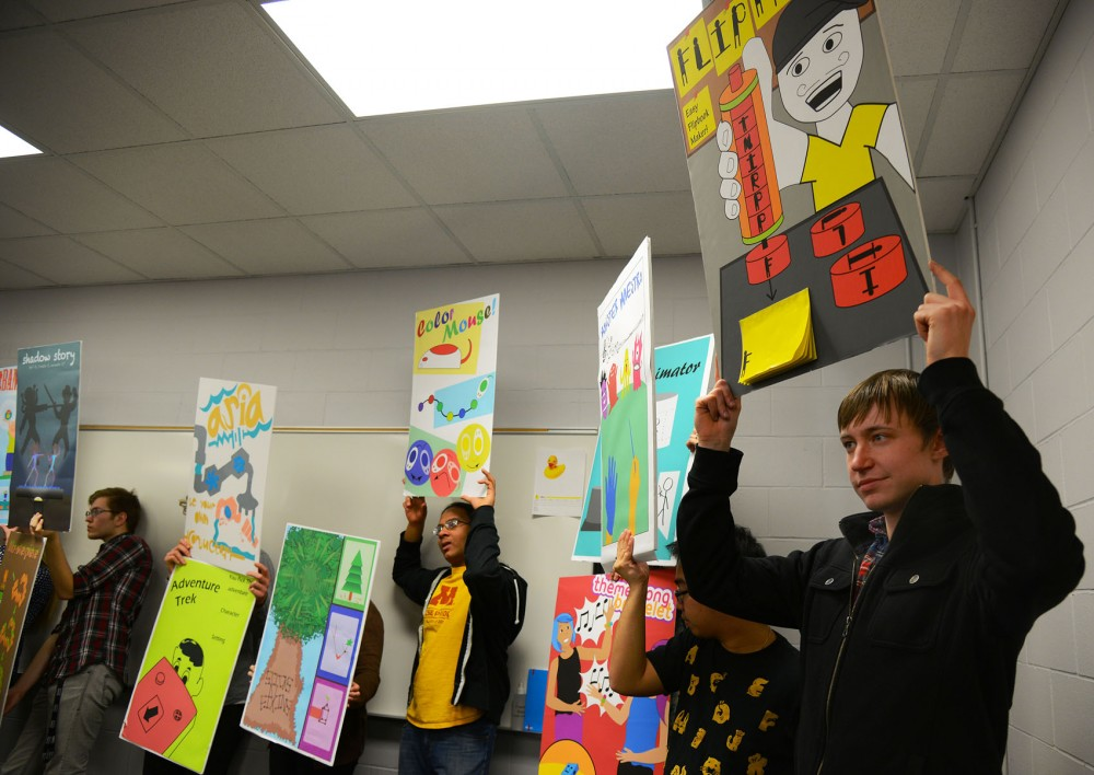 Toy design students hold up toy idea presentation boards after presenting in front of judges and lab instructors at the University of Minnesota Toy Lab on Wednesday.
