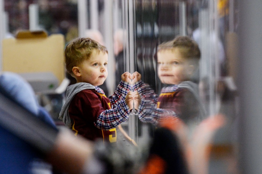 Gopher women's hockey fan Abraham Carter, 2, looks through the class to the rink, Saturday at Ridder Arena.