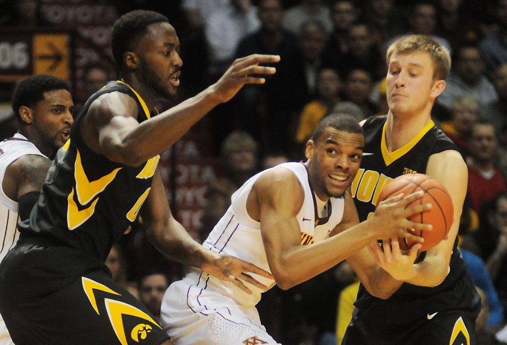 Minnesota guard Andre Hollins fights for the ball against Iowa on Tuesday night at Williams Arena.