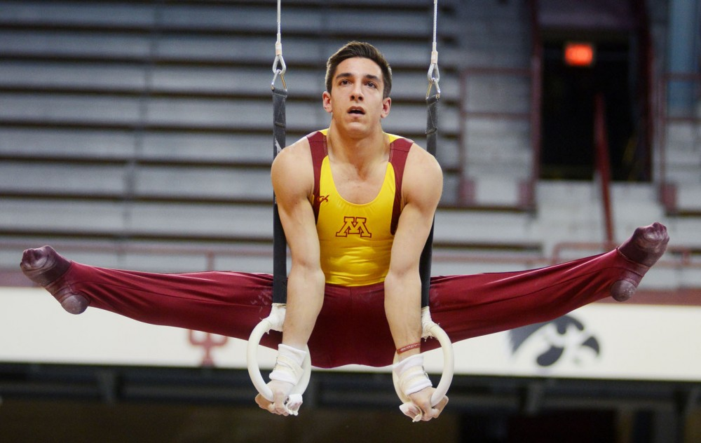 Minnesota junior Steve Jaciuk competes on the still rings at a meet against Iowa and Brockport at the Sports Pavilion on Saturday night. Saturday night was also senior night for the Mens Gymnastics Team.