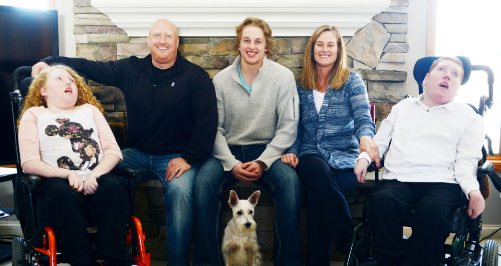 The Fasching family photographed at its Burnsville, Minn., home March 2. Hudson Fasching, middle, is a forward on the Gophers mens hockey team, and his two siblings, Mallory, far left, and Cooper, far right, have a condition that leaves them unable to walk or talk and requiring round-the-clock care.