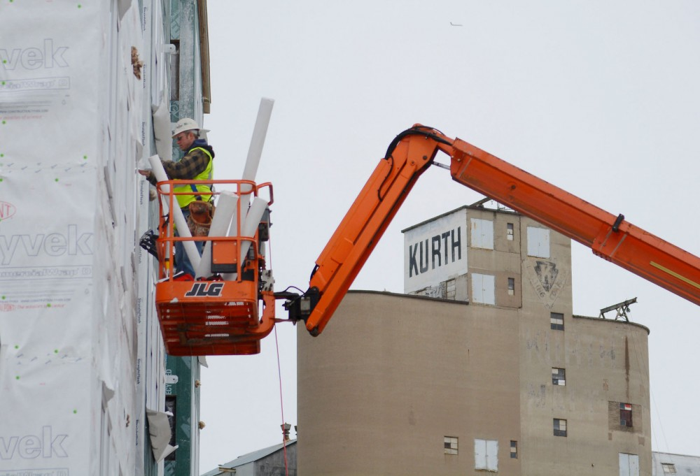 A construction worker in a cherry-picker works on the new student housing apartment complex being built by Weis Builders in Prospect Park on Tuesday afternoon.