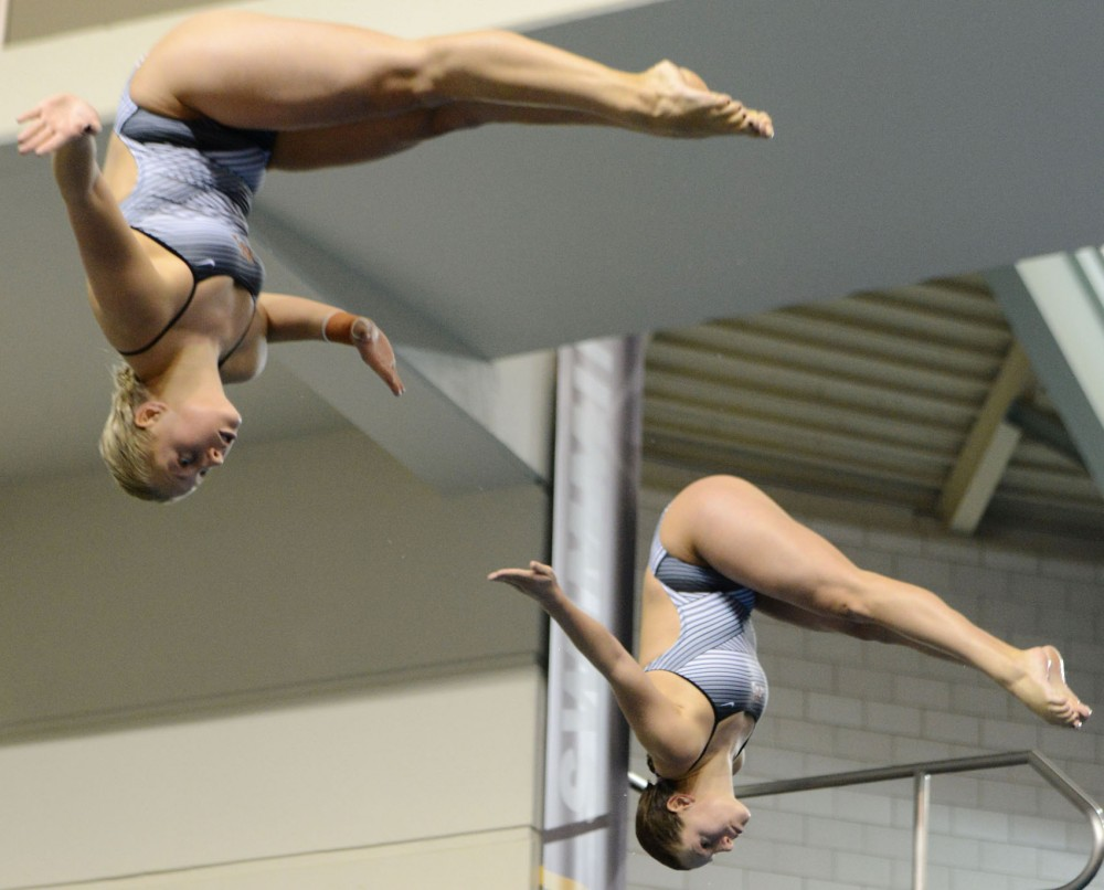 Minnesota's Maggie Keefer and Katie Grunawalt dive Wednesday, Feb. 20, 2013, at the University Aquatic Center.