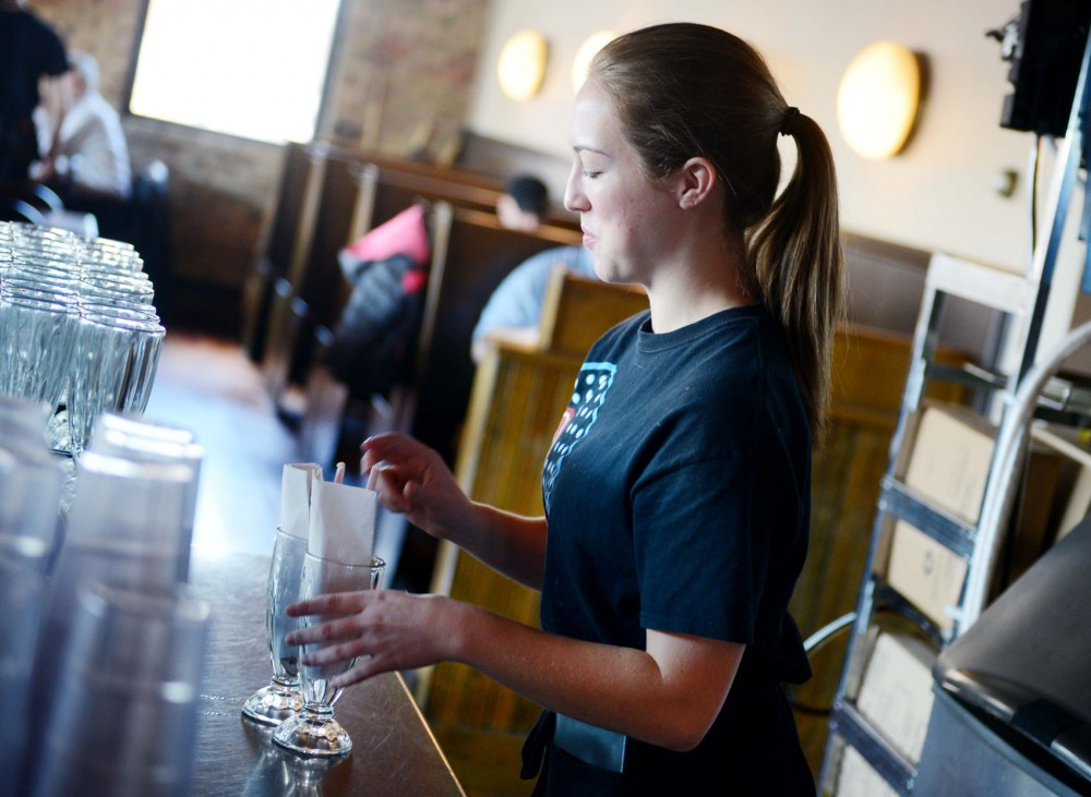 Server and former student Taylor Kuchera prepares malt glasses for customers at Annie's Parlour on Tuesday.  Minnesota law makers have proposed to change minimum wage from $6.15 to $9.50 which would affect many workers near the University of Minnesota.