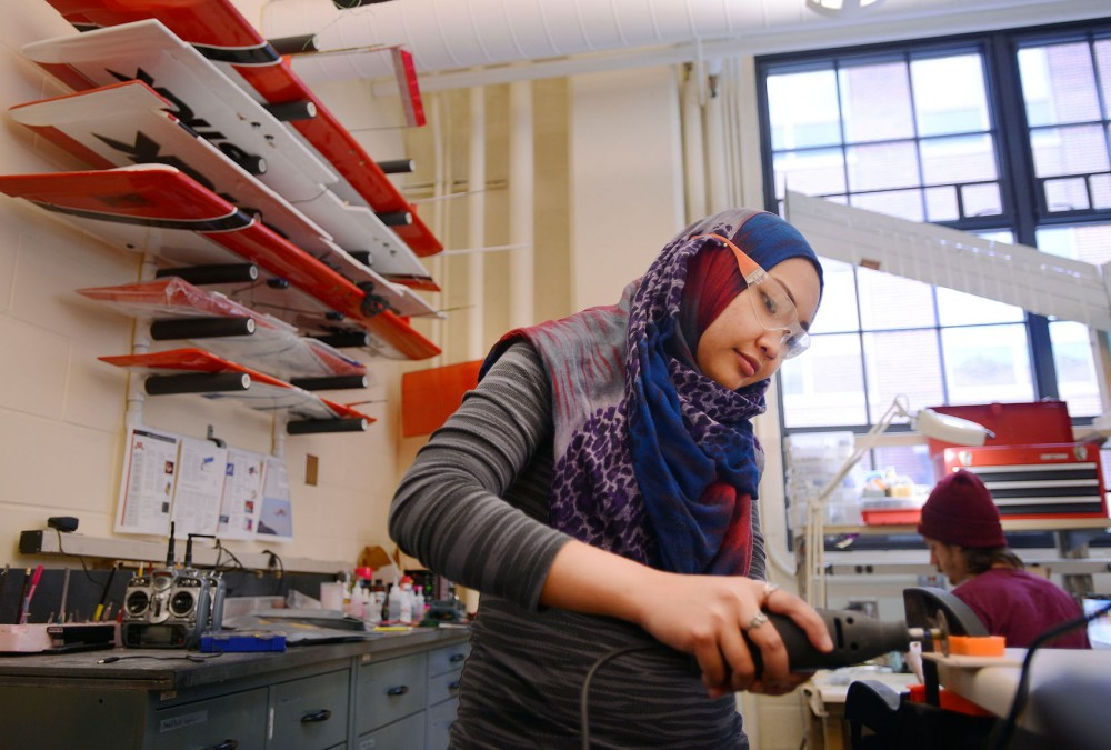 Khairunnisak Hamidun, a staff member in the Unmanned Aerial Vehicle lab, works on an aircraft that the lab is building for NASA in Akerman Hall on Tuesday.