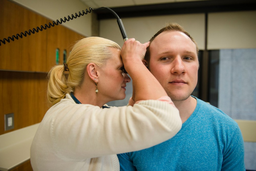 Doctor of nursing practice and family nurse practitioner student Sarah Melquist demonstrates nursing skills on family nurse practitioner student Mark Romportl at the Bentson Healthy Communities Innovation Center on Monday evening. As nurses continue to grow in Minnesota, a recent proposed bill in Minnesota could allow nurses more responsibility without doctoral supervision in order to combat a future doctor shortage.