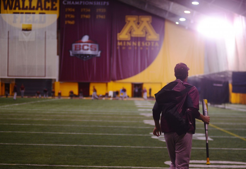 A Gopher baseball player prepares for practice Tuesday night at the Gibson-Nagurski Football Practice Complex. Minnesota's baseball and softball teams work to share the facility with the football team during the spring.