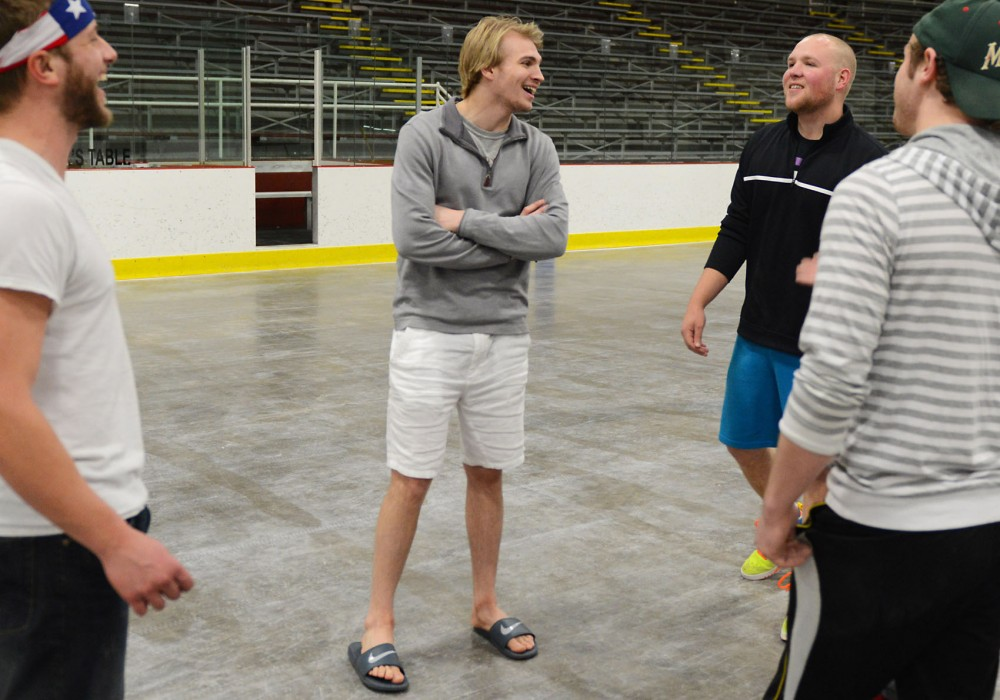 Minnesota goalie Adam Wilcox, pictured second to the left, catches up with old high school teammates at Wakota Arena in South Saint Paul on Sunday. Wilcox grew up playing youth hockey at Wakota Arena before playing for the Gophers.