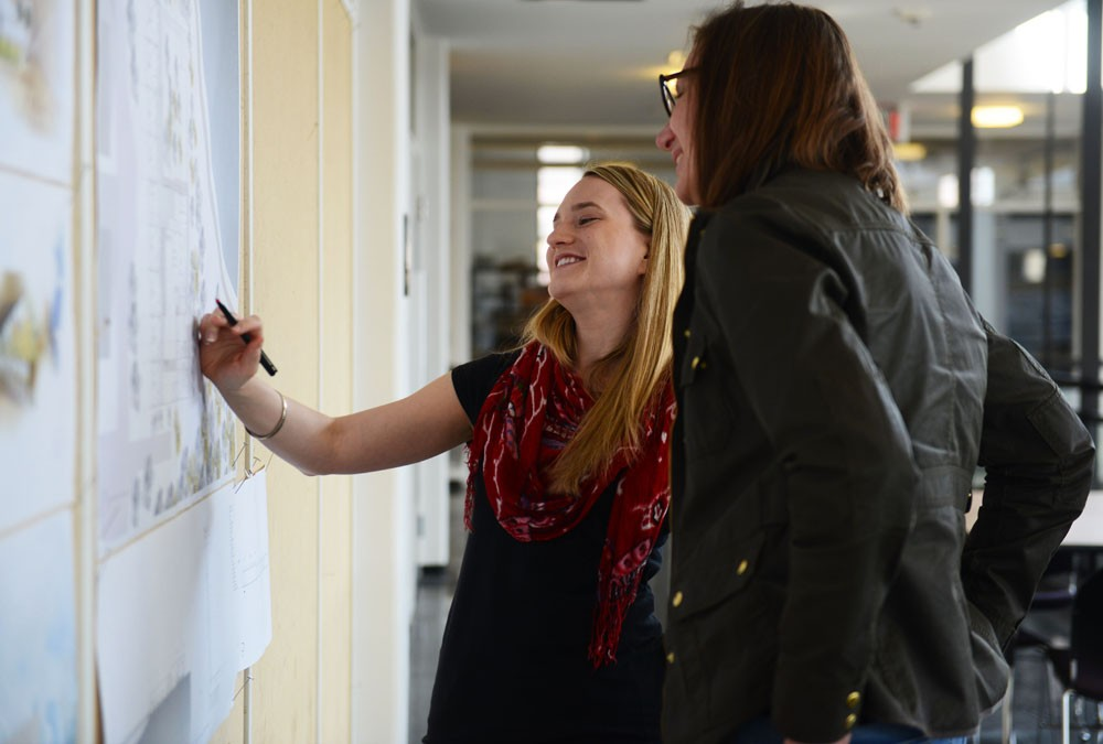 Architecture Graduate Student Sophia Skemp shows her final project to previous graduate student and professional architect Julie Macleod in Ralph Rapson Hall on the University's East Bank on Monday.  Professionals were viewing the graduate students' work and giving them advice.